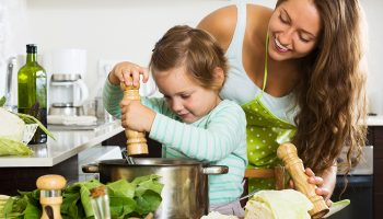Happy family cooking potatoes soup  at home kitchen